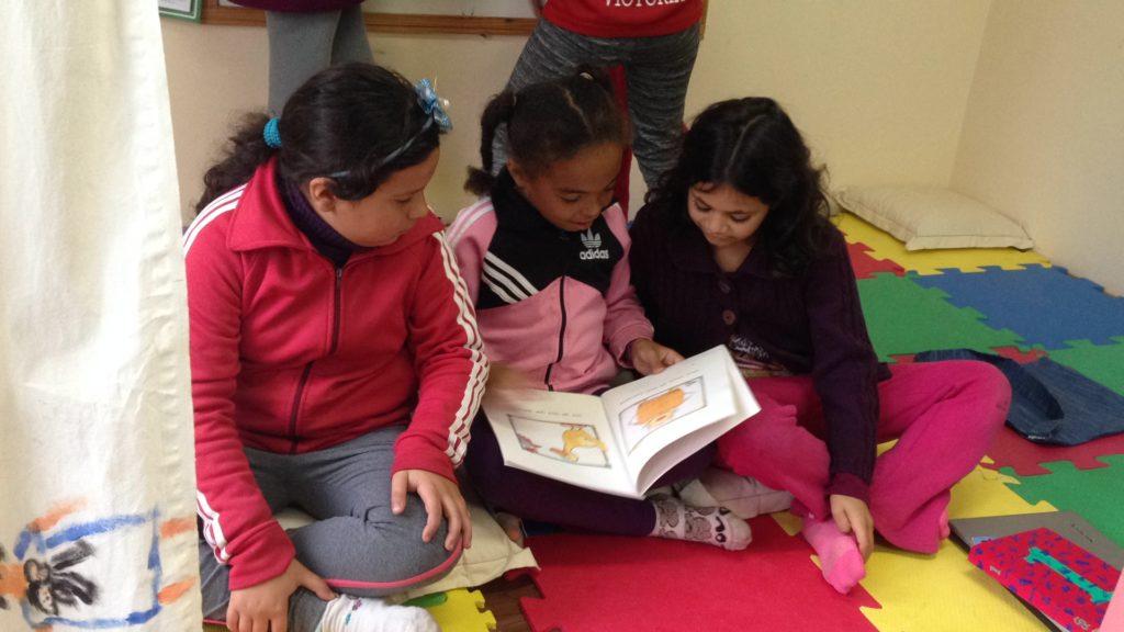 Tre jenter leser i en bok