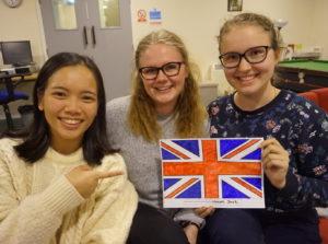 Bildet viser tre av ucrewerne 17/18 til England sammen med et britisk flagg de har fargelagd.