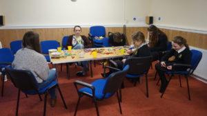 Bildet viser noen av jentene ved drop in-en i St Mike`s kirka i Carlisle, godt i gang med å lage vennskapsarmbånd.