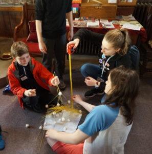 Bildet viser Anna sammen med laget hennes, hvor hun måler spagettitårnet de har laget.