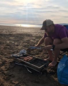 Bildet viser Kristian Tjemland som griller på stranden.