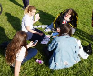 Bildet er et illustrasjonsbilde som viser ungdom som spiller kort i parken.