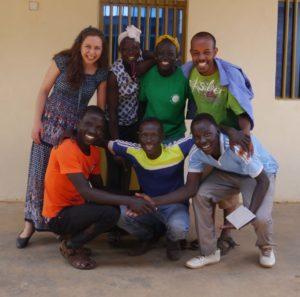 En gruppe på sju unge mennesker smiler