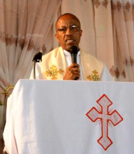 Bildet viser den nye kirkepresidenten Rev. Yonas Yigezu på talerstolen
