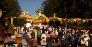 bildet viser mange festkledde ortodokse personer foran en ortodoks kirke