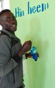 En mann skriver en tekst på en vegg