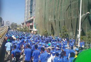 Bildet viser mange folk i blå T-skjorter som går på gatene i Addis Ababa