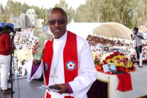 Bildet viser en prest med et kors på en scene med mange mennesker i bakgrunnen