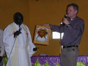 Bildet viser presten og gjesten ved overrekkelsen av et bildet