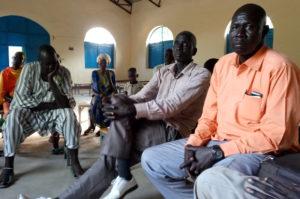 Bildet viser flere menn som sitter inne i eet kirkerom