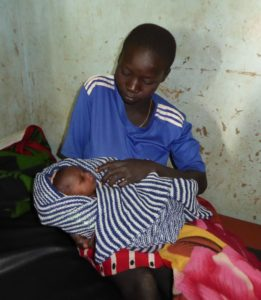 Bildet viser ei mor med en nyfødt baby tullet i et håndstrikket teppe