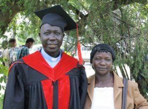 En mann og en kvinne, mannen med kjole og hatt etter graduation - i hagen til Mekane Yesus Seminary.