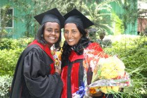 To kvinner i en part - med kjoler, hatter og blomsternukett etter graduation seremoni