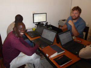 Tre personer sitter rundt et bord og jobber med PCer
