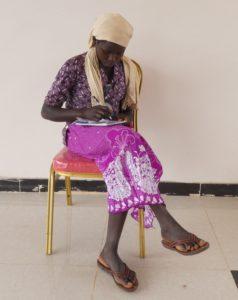 En Mao jente sitter på en stol og skriverned noen stikkord for en bibelhistorie