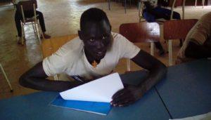 Ung gumuz mann sitter ved et bord og leser i ei bok
