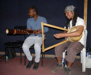 Bildet viser 2 musikere med et tradisjonelt gassisk og etiopisk musikkintstrument