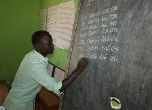 Morsmålslærer skriver setninger på Gwama på tavlen