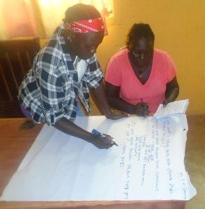 Bildet viser 2 kvinner som skriver på et stort ark
