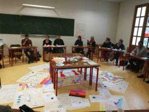 Bilde vier et klasserom hvor studentene sitter i sirkel med sine kreative produkter samlet i midten