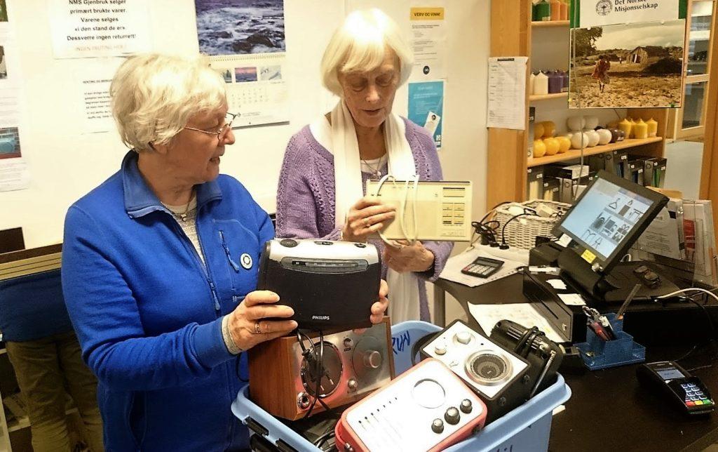 Oddveig Øygard og Anne Marie Stoknes til høgre med en av kassene med radioer de har fått inn til NMS Gjenbruk i Ålesund.